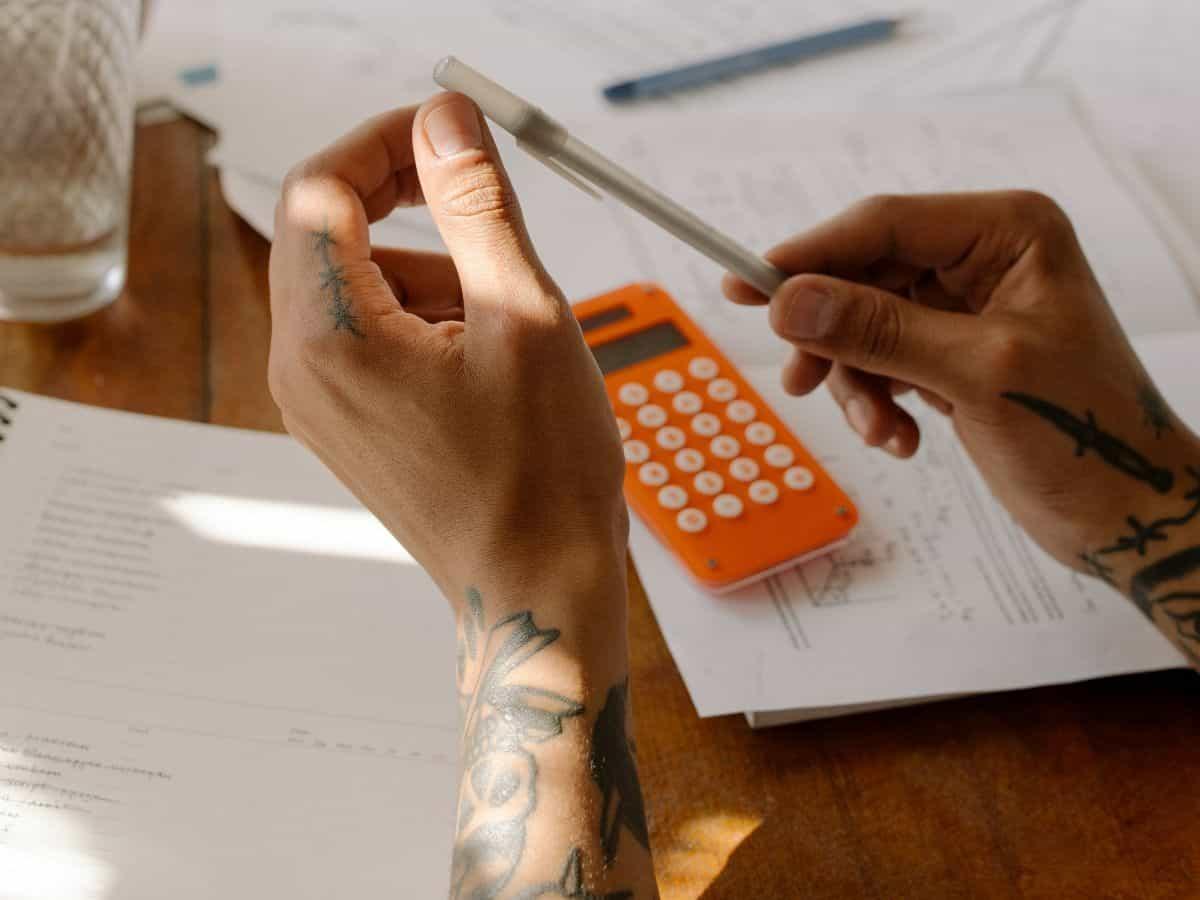 two hands, orange calculator, pen and paper