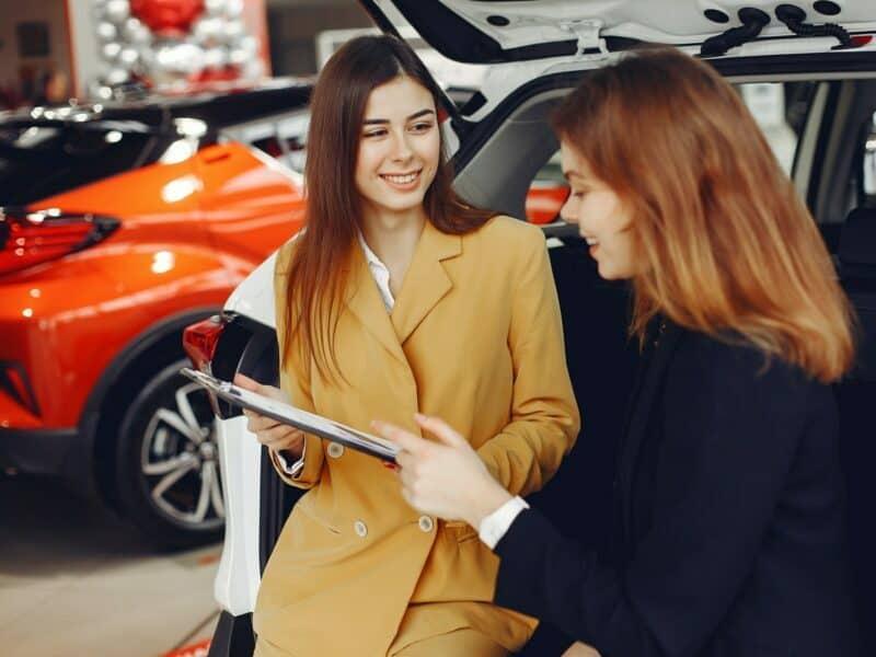 A woman speaks to a sales associate inside of a car dealership.