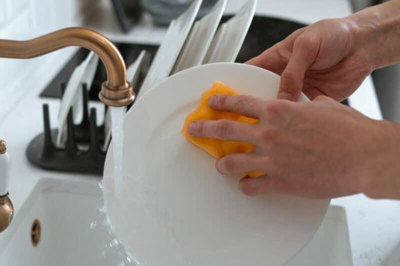 A hand holding a bright orange sponge is wiping a white plate as water flows from a trendy gold faucet.
