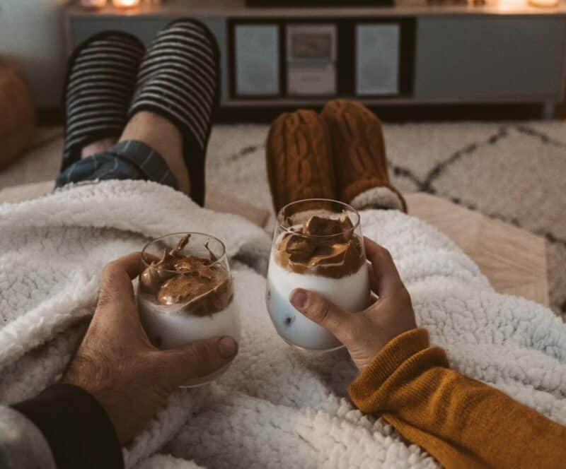 A man and woman holding a winter beverage as they sit with a fluffy blanket and their slippers kicked up.