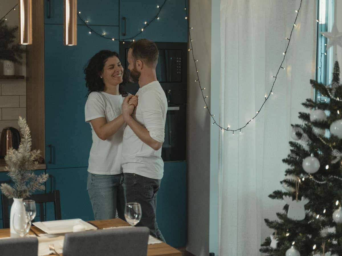 couple dancing in room with christmas tree