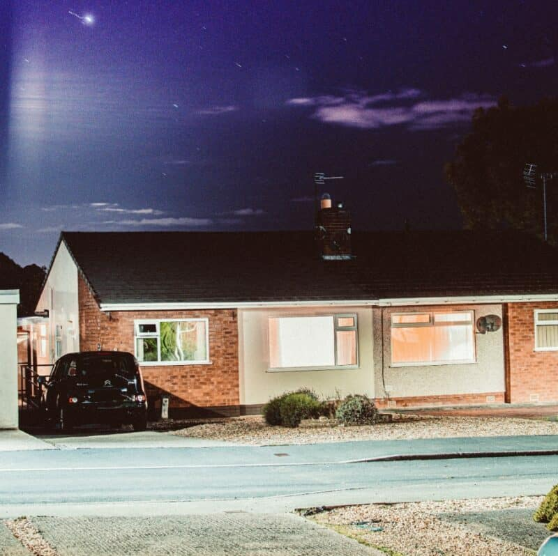 The front yard of a one-story home at night.