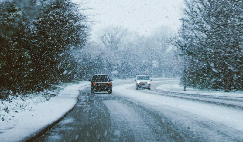 Two vehicles driving on opposite sides of the road as snow falls from the sky.