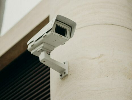 A white security camera installed on a modern, cement beige wall outside.
