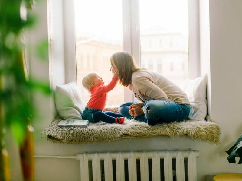 mom and baby in front of window