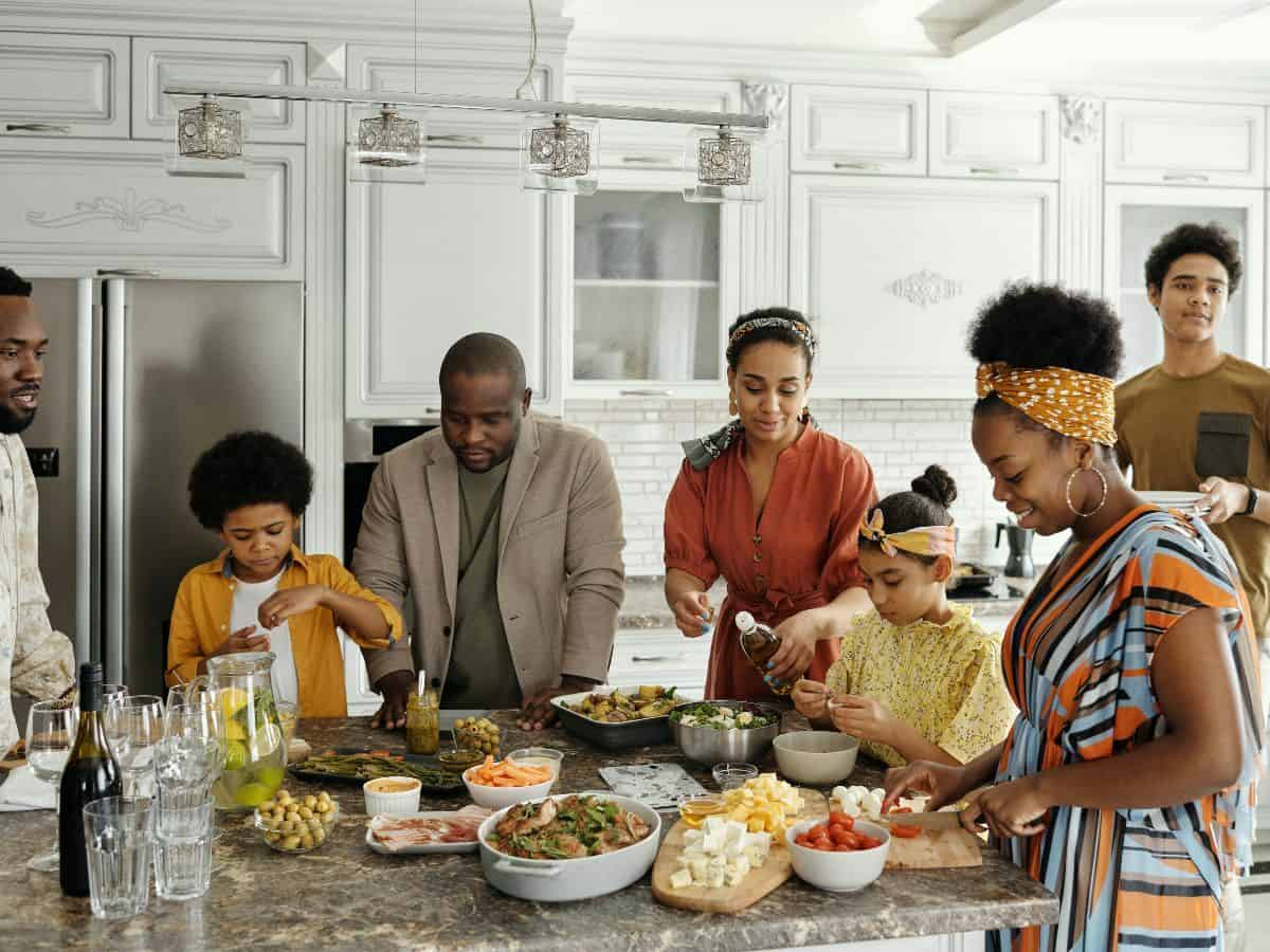 family in kitchen with food and water on the counter