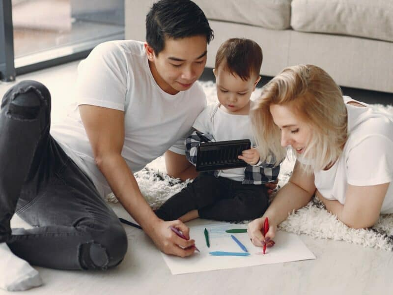 A man and woman coloring on the floor with their young child.