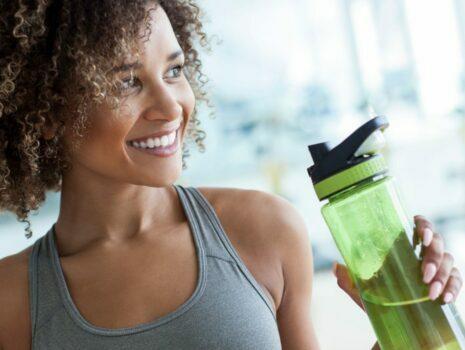 woman in gray tank top holding green water bottle