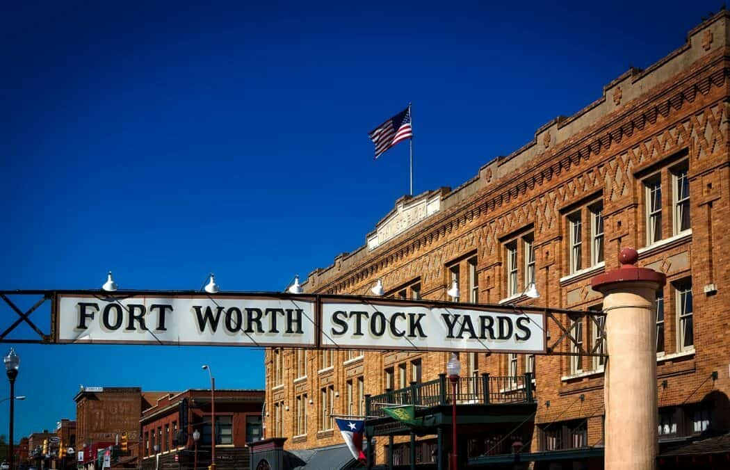 """Historical buildings holding up a banner reading """"Fort Worth Stock Yards""""."""