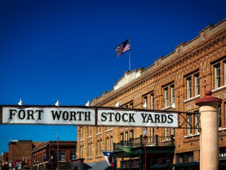 "Historical buildings holding up a banner reading ""Fort Worth Stock Yards""."