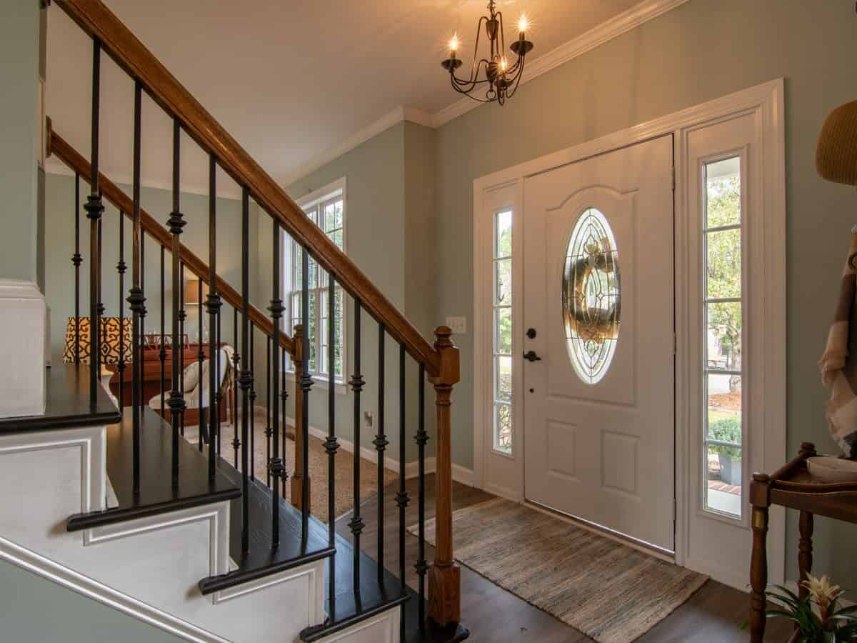 pov facing the front door of a house with stairs on left side