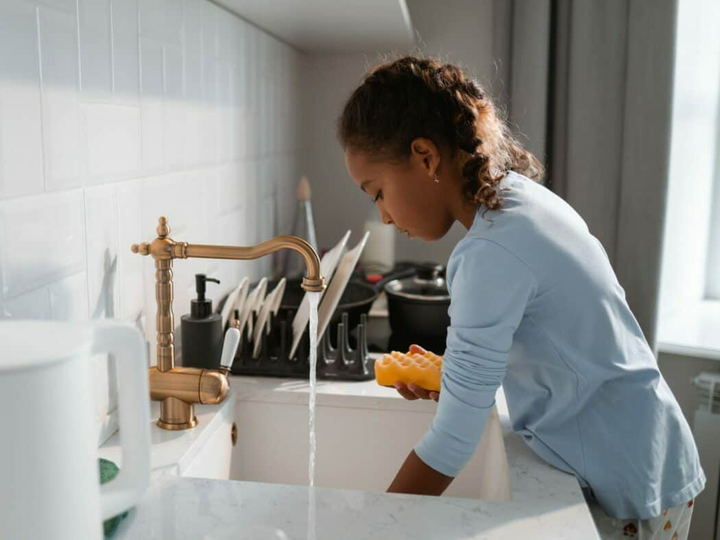young girl in blue shirt doing dishes