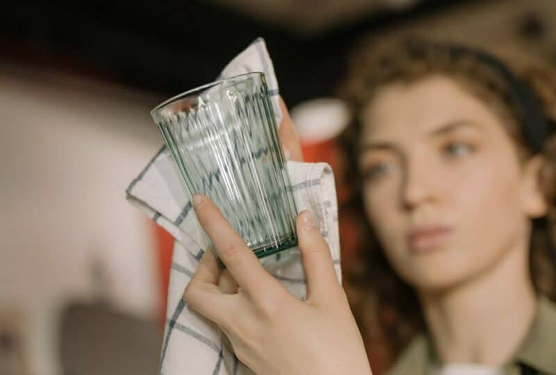 A woman is closely examining the glass she is cleaning with a towel.