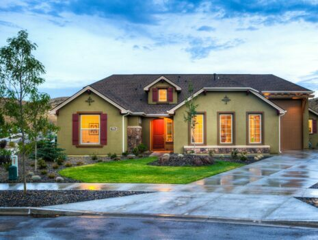 A one-story green stucco home with a sizable driveway.