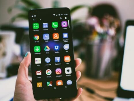 Closeup of a hand holding a black smartphone that's opened to the home screen with rows of applications.