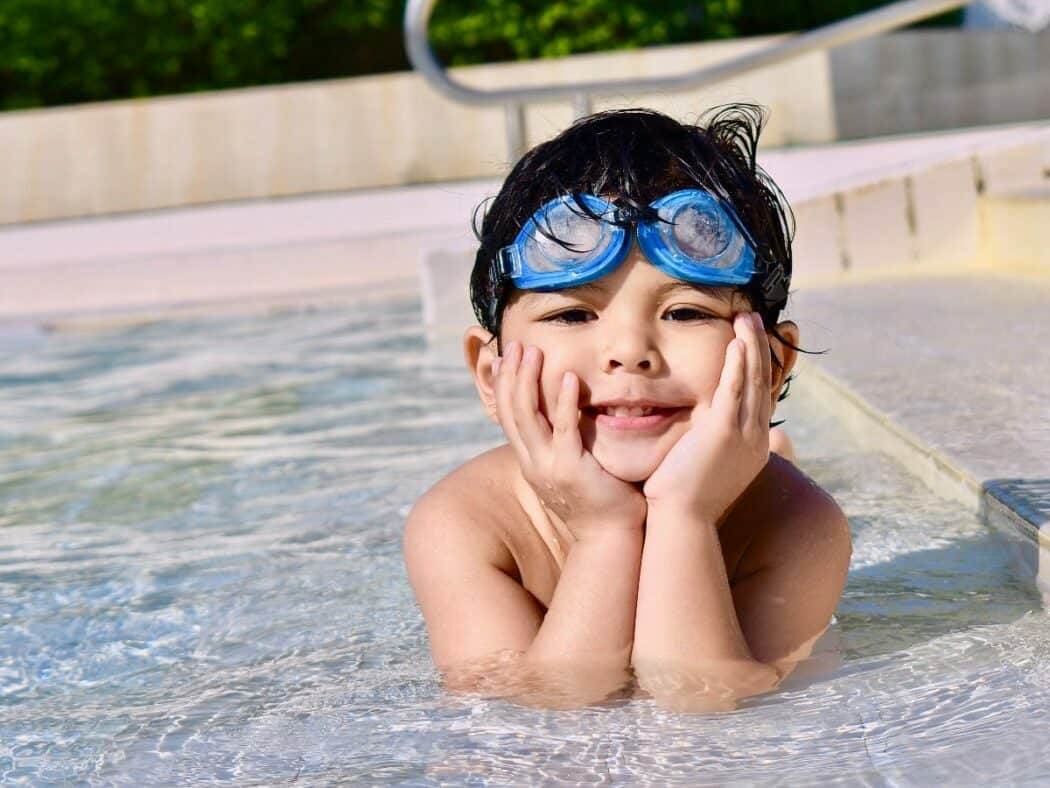 kid in pool with blue goggles