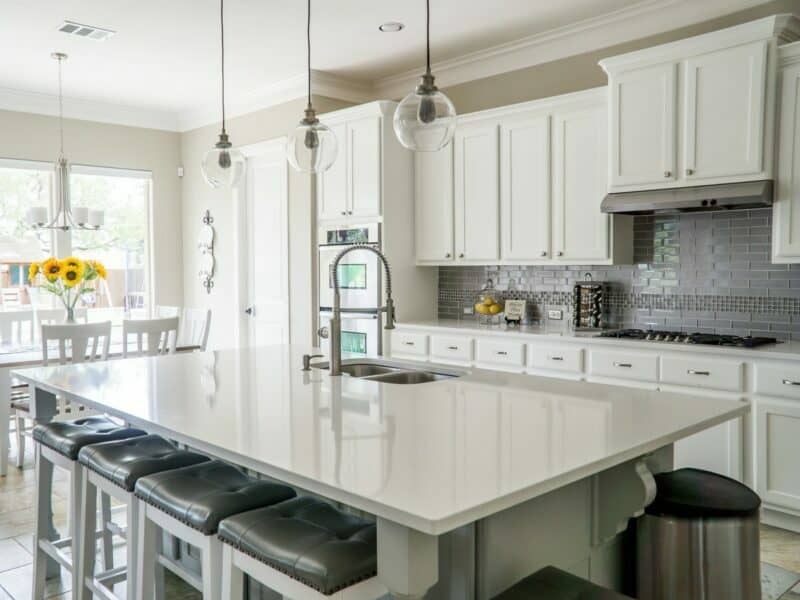 A clean and shiny granite kitchen counter inside of a modern kitchen with white cabinets and dangling light fixtures.