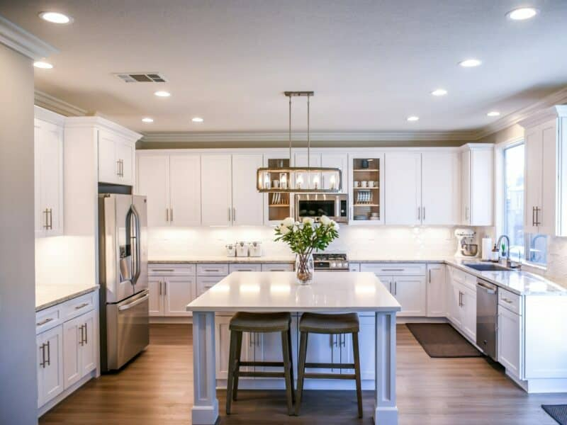 A modern kitchen with white cabinets and stainless steel appliances.