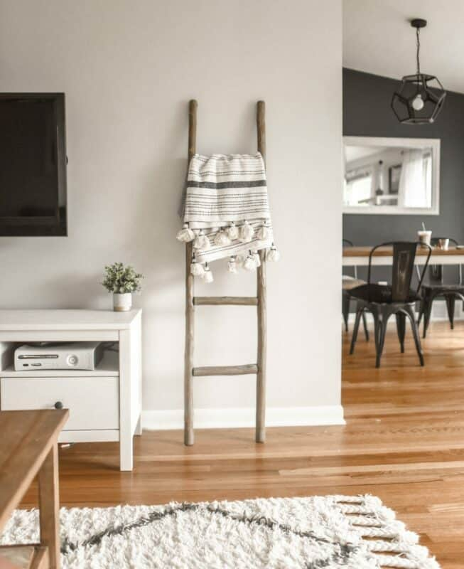 A trendy living room with a blanket ladder next to a white tv stand and television.