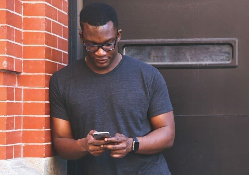 A man wearing glasses looks down at his smartphone as he stands outside next to a red brick building.