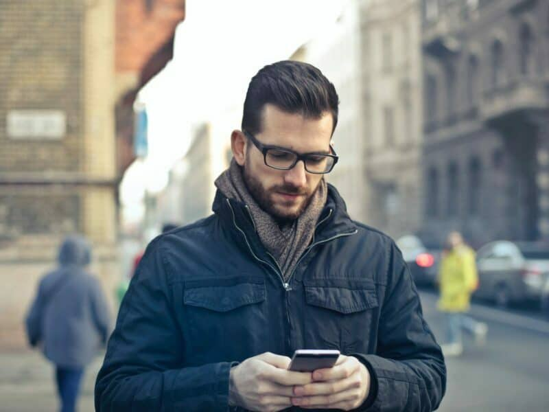 man in glasses looking down at phone while walking