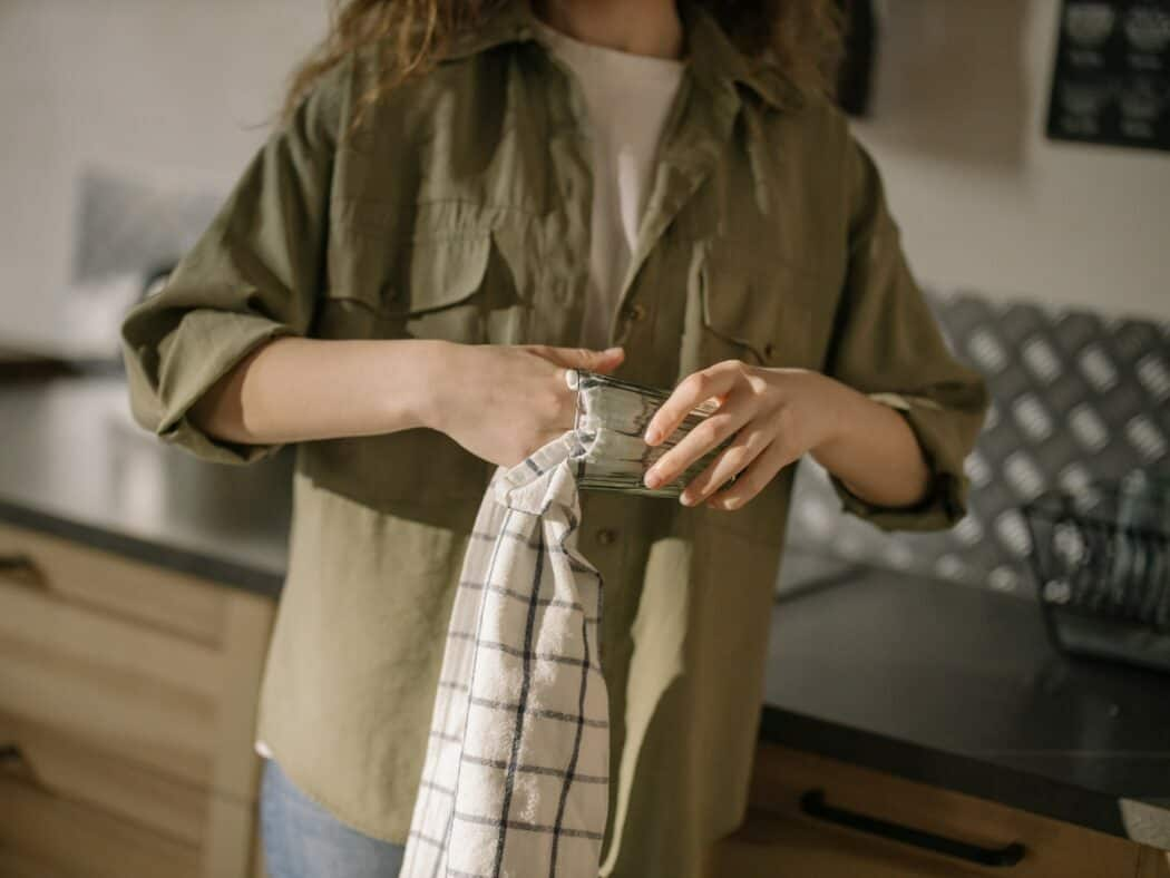 woman in green cardigan dries dishes with towel