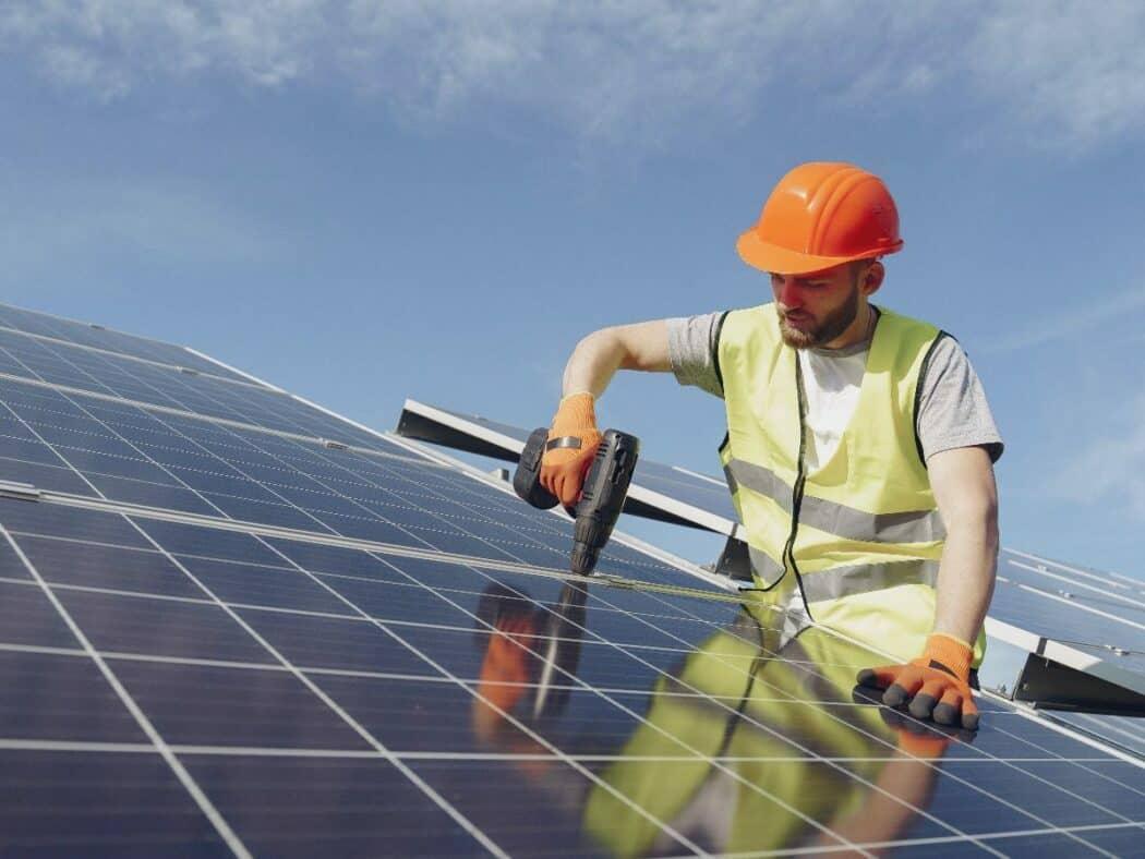 man in orange hard hat installing solar panels