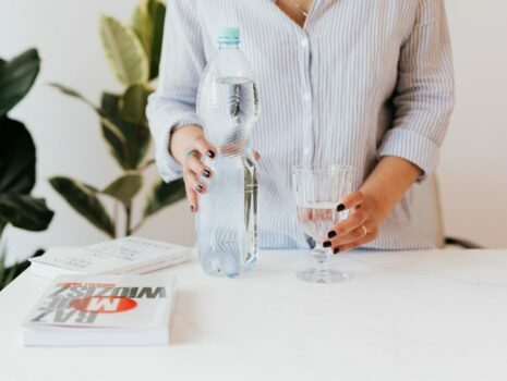 woman in button down shirt with bottled water and water in glass
