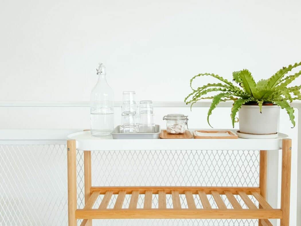 Pitcher of water on a white cart with glasses and a potted house plant.