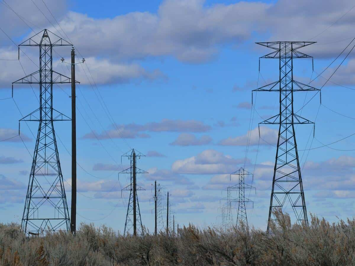 Powerlines standing in a field beneath a light blue sky with clouds.