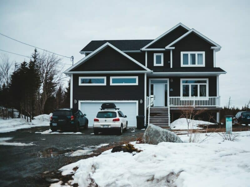 Two SUVS are parked in the driveway of a modern, two-story home surrounded by snow.