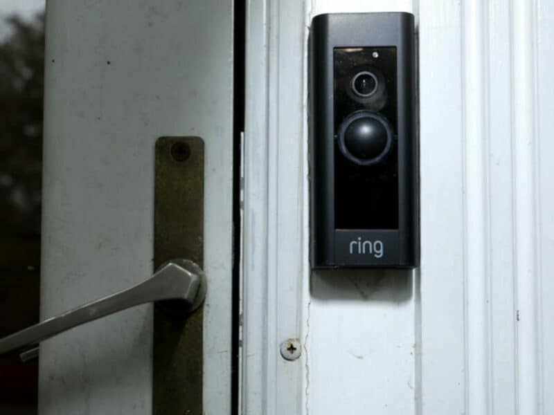 closeup of the ring doorbell camera on white siding with door handle in background