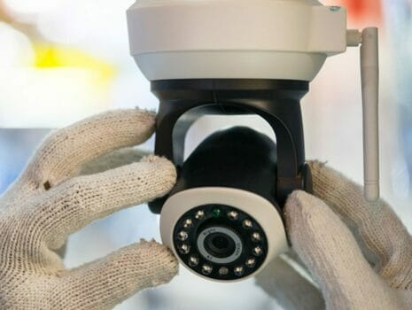 two gloved hands installing security camera