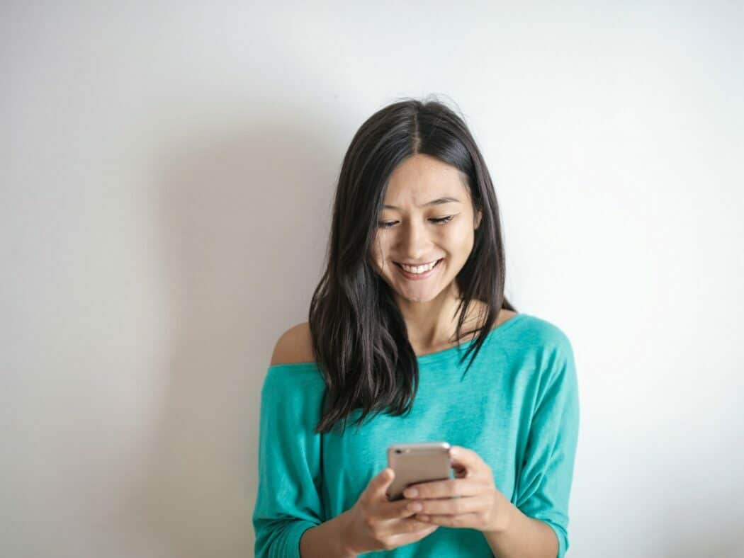 A woman wearing a teal t-shirt is looking down at her smartphone and smiling.