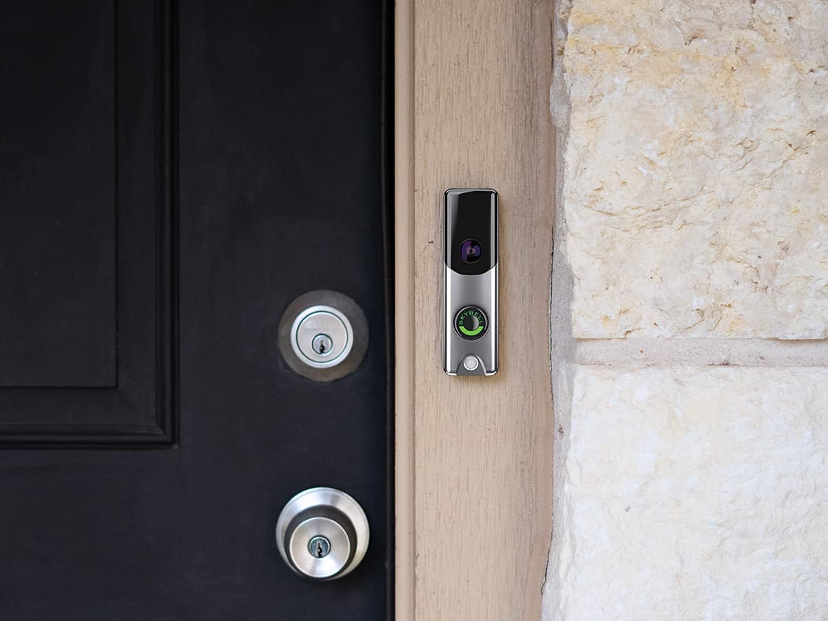 A silver Skybell doorbell camera is installed next to a black front door.