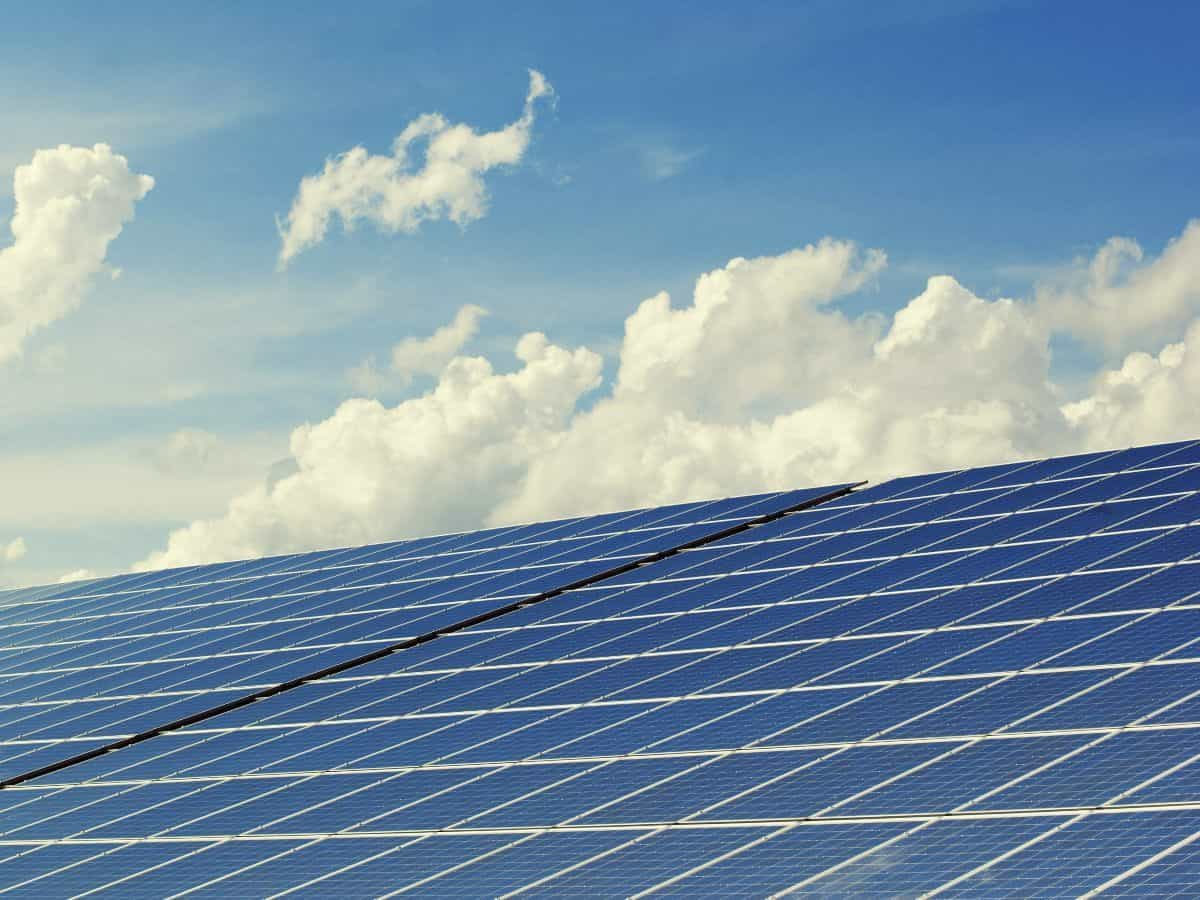 solar panels with blue, cloudy sky in the background