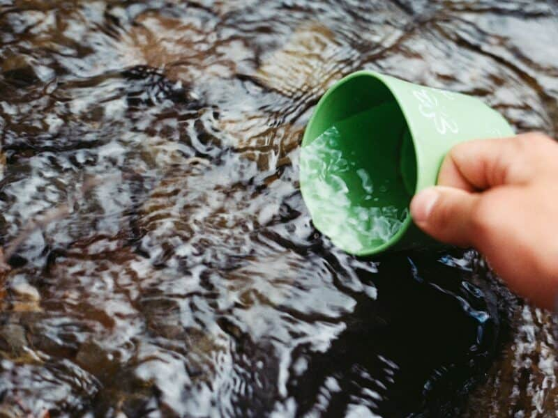 A hand is filling a green cup with water from a spring outdoors.