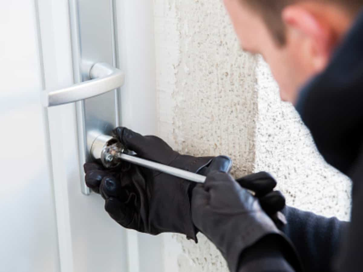 burglar in black gloves using a tool to enter home