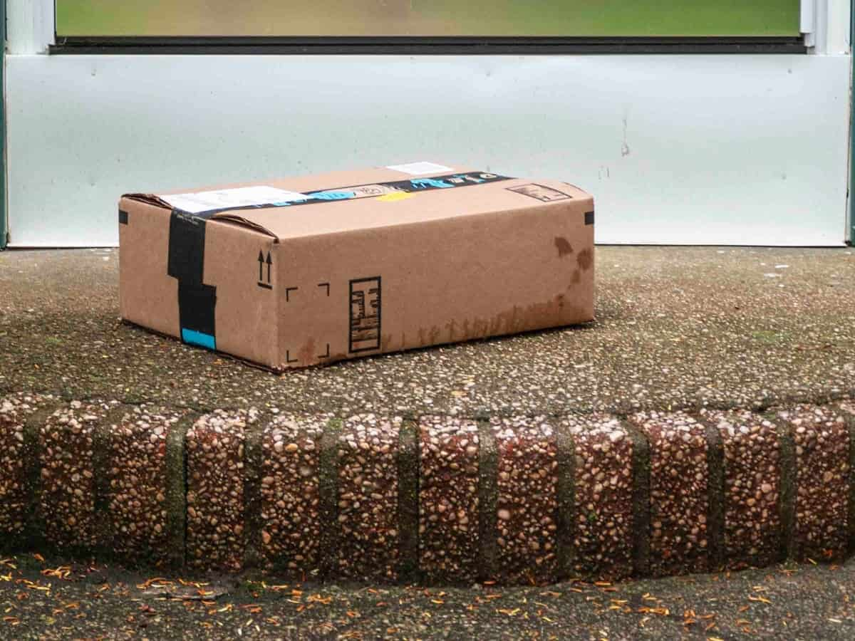 a package is left at the white front door on the brick