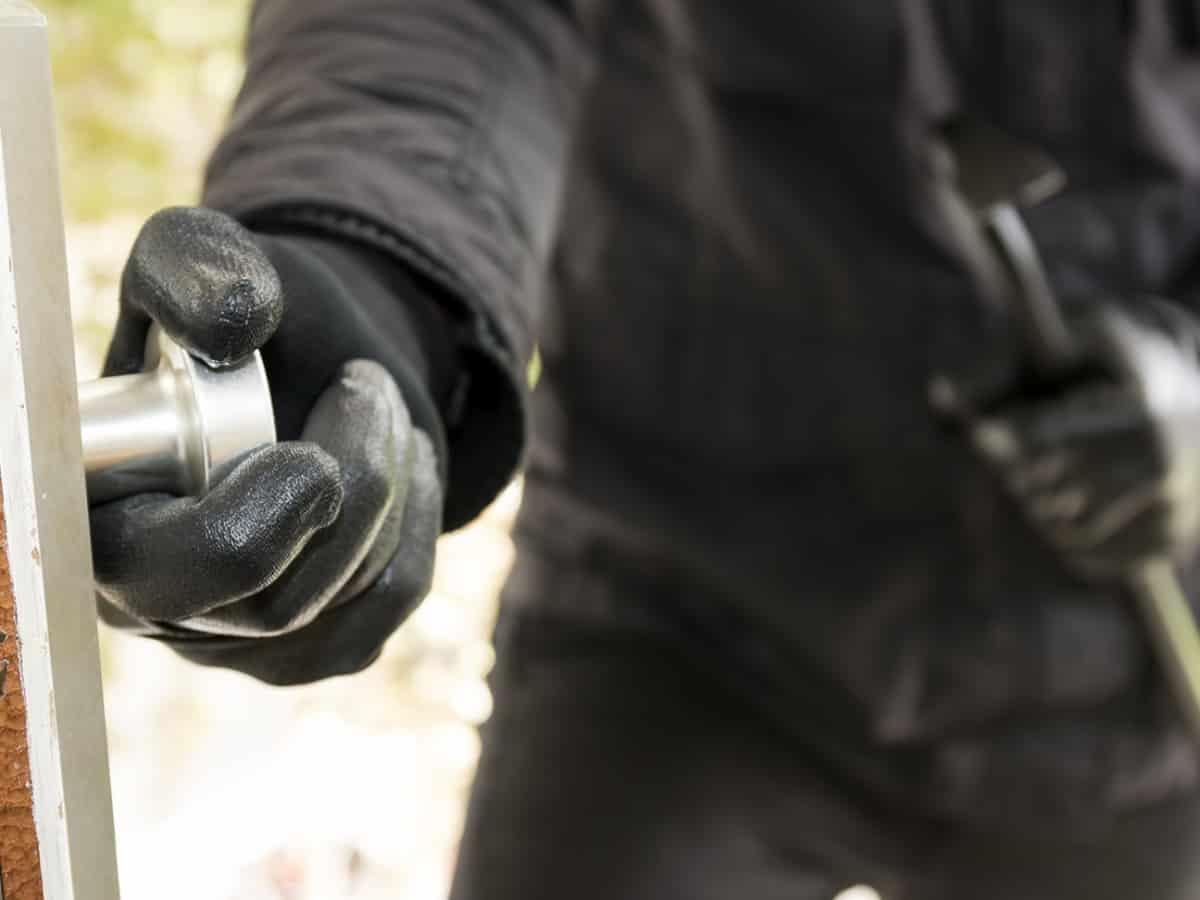 burglar in black gloves forcefully entering door