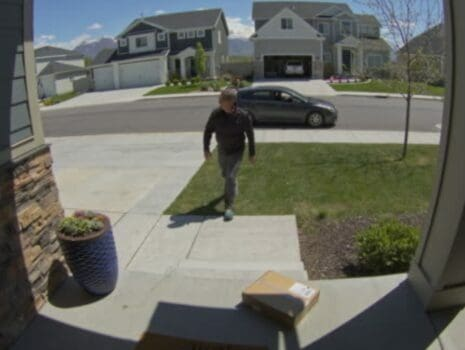 doorbell camera footage of package theft, car in background