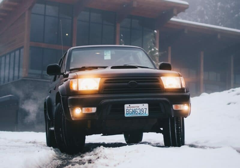 A large SUV with glowing headlights is sitting in snow outside of a rustic home ready to drive off.