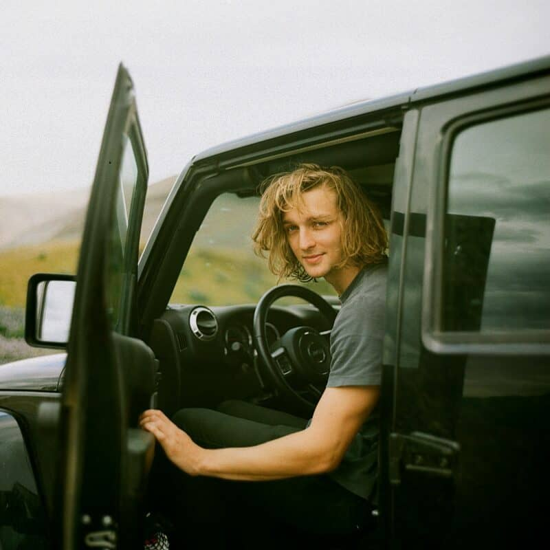 A young man sits with the door open inside of a black used car that's outdoors.