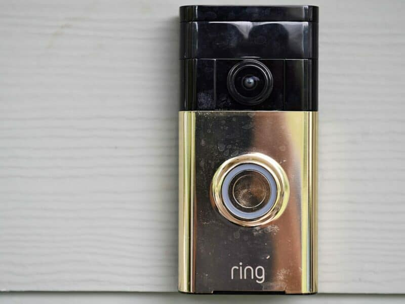 a gold ring doorbell camera against white wall
