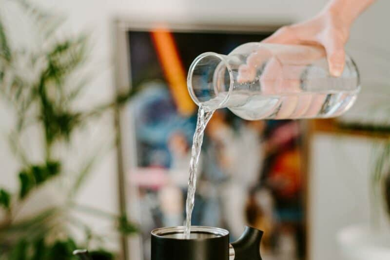 A hand pouring water from a glass carafe into a black teapot kettle.