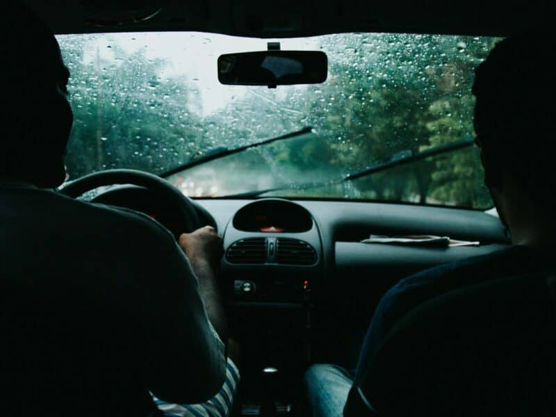 Windshield wipers are wiping away rain as two passengers ride inside a vehicle driving down a road.