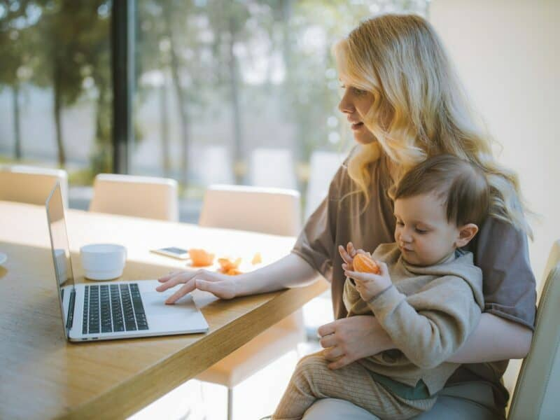 A young woman with blonde hair is holding her baby that's playing with an orange as she scrolls on her laptop at a kitchen table.