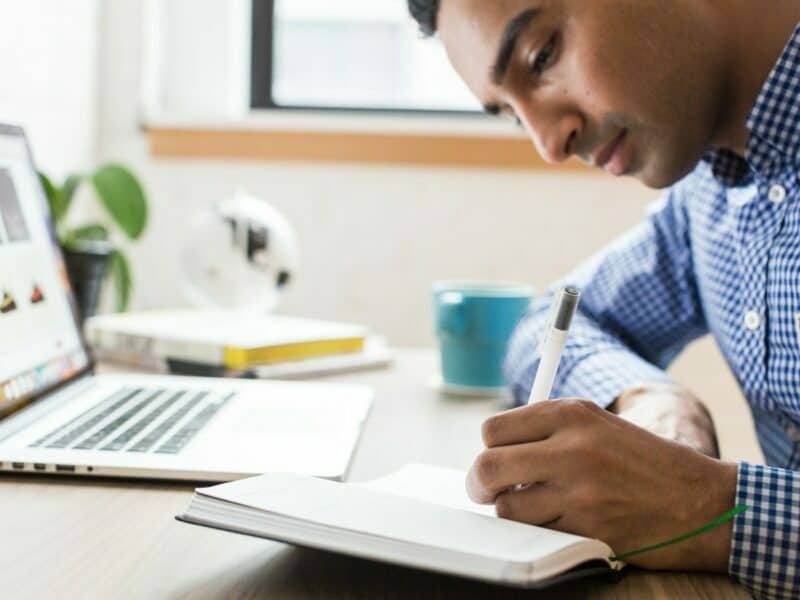 A young man is writing inside of a notebook at a desk holding his laptop, coffee cup, and small stack of books.