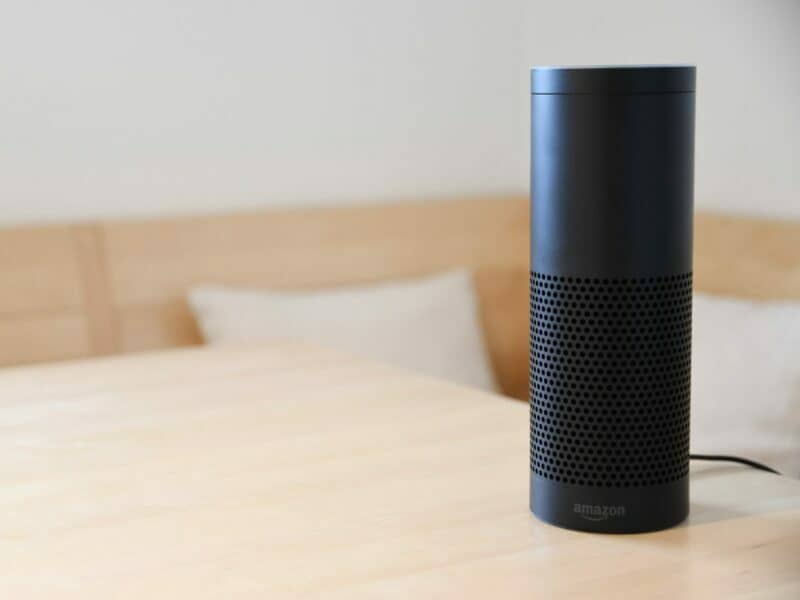 an amazon alexa, black and on wooden table