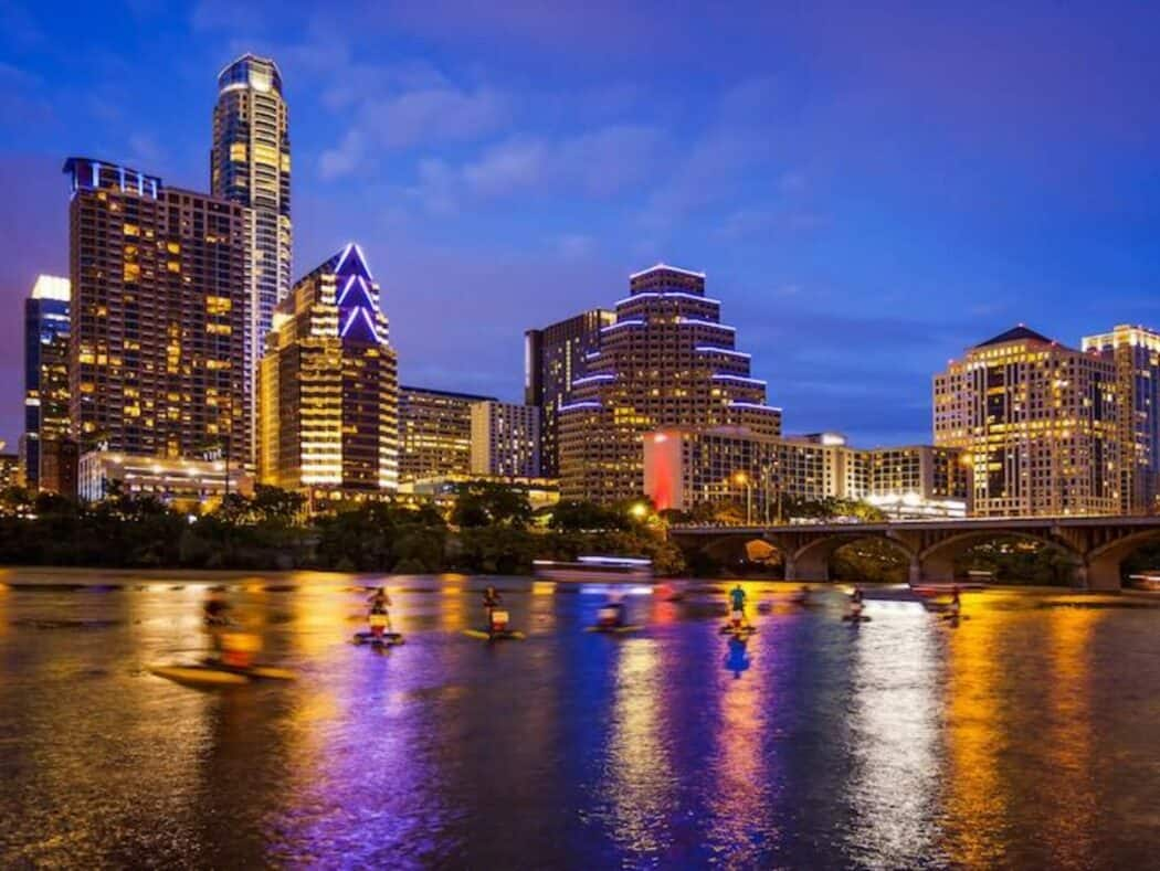 Austin, Texas downtown skyline at night on the Colorado River as unidentified tourists ride water bikes